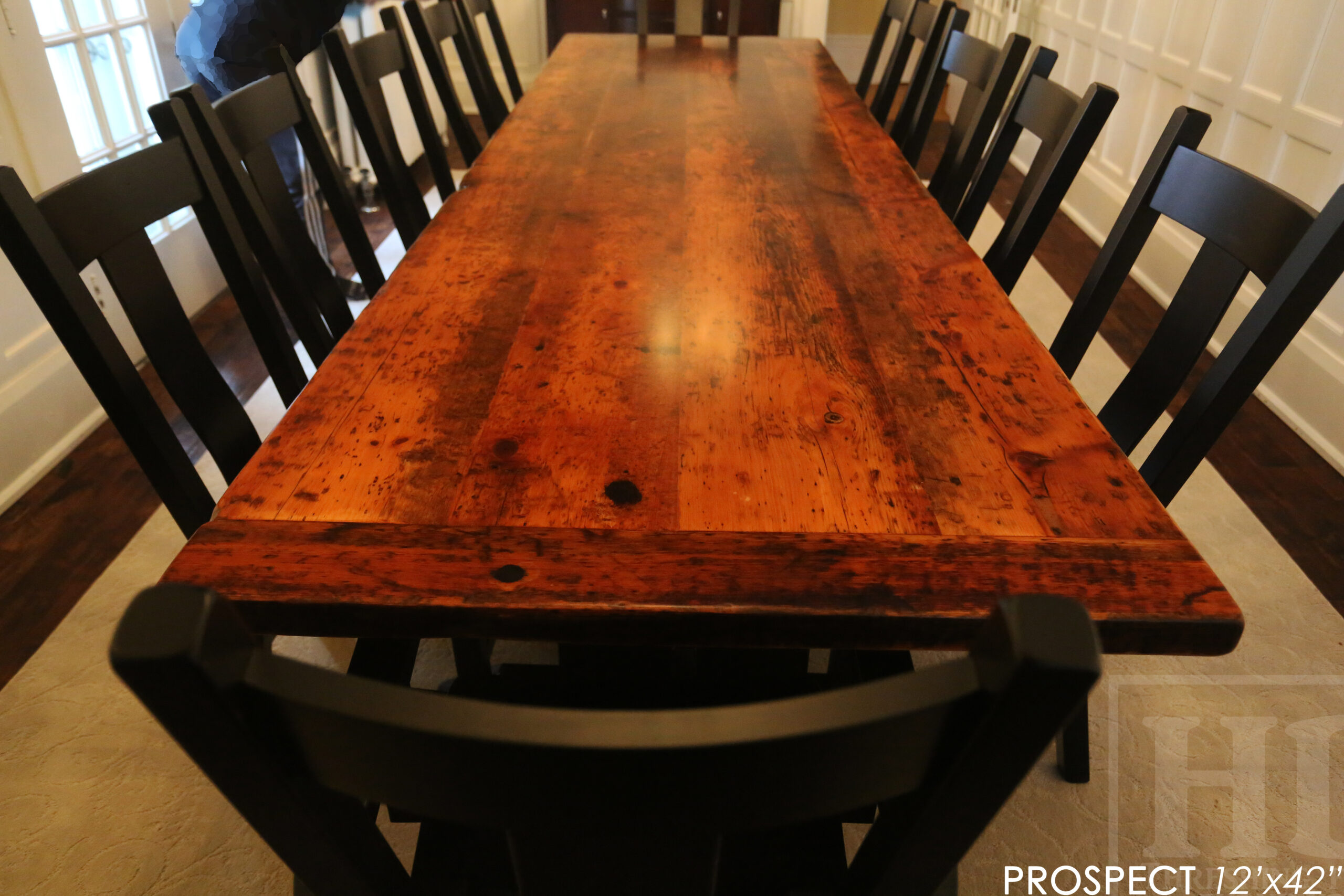 """12' Reclaimed Wood Table for a Port Dover home - 42"""" wide - Trestle Base - 2"""" Old Growth Pine Threshing Floor Construction - Original edges & distressing maintained - Premium epoxy + satin polyurethane finish - Black Painted Base - 12 Plank Back Chairs / Wormy Maple - Painted Solid Black / Satin polyurethane clearcoat finish - www.table.ca"""